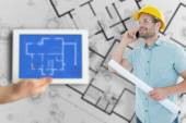 Architect with blueprint talking on mobile phone — Stockfoto