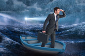 Businessman in boat against stormy sea — Stock Photo