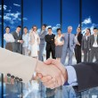 Composite image of smiling business people shaking hands while l — Stock Photo #73190545