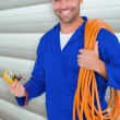 Electrician with wire roll and multimeter — Stock Photo #73194699