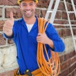 Technician with wire roll gesturing thumbs up — Stock Photo #73194929
