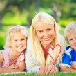 Mother with her children lying down — Stock Photo #73195013