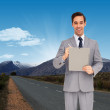 Happy businessman holding a clipboard — Stock Photo #73199623