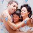 Happy family lying in bed — Stock Photo #73199689