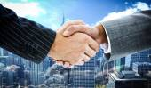Business people shaking hands against skyline — Stock Photo