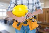 Technician holding hammer and hard hat — Foto Stock