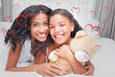 Composite image of pretty woman lying on bed with her daughter s — Stock Photo