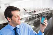 Smiling businessman showing smartphone to camera — Foto de Stock