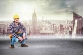 Crouching handyman holding power drill — Stock Photo