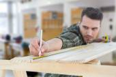 Worker marking on wooden plank — Stock Photo