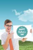 Composite image of geeky hipster smiling and showing card — Stock Photo