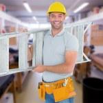 Smiling repairman carrying ladder — Stock Photo #73200743