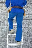 Carpenter climbing step ladder — Stock Photo