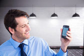Smiling businessman showing smartphone — Foto de Stock