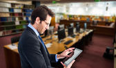 Businessman standing while using tablet — ストック写真