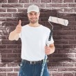 Happy man with paint roller gesturing thumbs up — Stock Photo #73222293