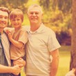 Grandfather father and son with family in background at park — Stock Photo #73222525