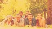 Extended family lying on grass in the park — Stock Photo