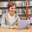 Smiling teacher using tablet pc at library — Stock Photo #73263539