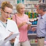 Pharmacist writing on clipboard — Stock Photo #73267941