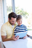 Father and son using tablet pc — Stock Photo