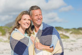 Happy couple wrapped up in blanket  — Stock Photo