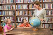 Pupils and teacher looking at globe in library — Stock Photo