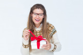 Geeky hipster smiling and holding present — Stock Photo