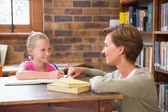 Teacher helping pupil in library — Stock Photo