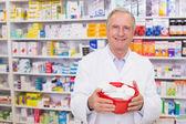 Senior pharmacist holding bowl of medicines — Stock Photo