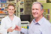 Pharmacist and costumer smiling a camera — Stock Photo