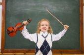 Cute pupil holding violin and violin string — Stock Photo