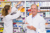 Pharmacists searching medicines with prescription  — Stock fotografie