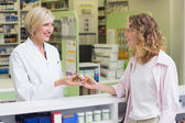 Pharmacist and costumer holding medicine jar  — Stock Photo