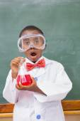 Surprise pupil holding at a red liquid — Stock Photo