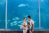 Casal feliz ao lado do tanque de peixes — Fotografia Stock