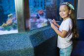 Cute girl looking at fish tank — Stock Photo
