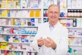 Smiling pharmacist holding a box of pills — Stock Photo