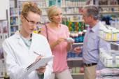 Pharmacist writing on clipboard — Stok fotoğraf