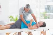 Doctor stretching a young man back  — Stock Photo