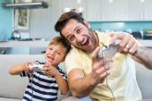 Father and son playing video games together — Stock Photo