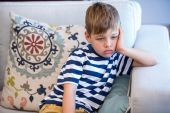Tired little boy on the couch — Stock Photo