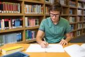 Φοιτητής κάθεται στη βιβλιοθήκη και το γράψιμο — Φωτογραφία Αρχείου
