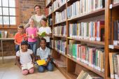 Teacher and pupils smiling at camera at library — Stock Photo