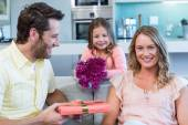 Father and daughter surprising mother with gift — Stock Photo