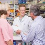 Pharmacist giving prescription to costumer — Stock Photo #73270977