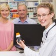 Pharmacist showing medicine jar to a customers — Stock Photo #73275879