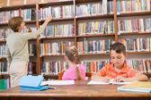 Profesor buscando un libro en la biblioteca — Foto de Stock