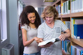 Students reading together in the library  — Stock Photo