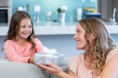 Daughter surprising mother with gift — Stock Photo